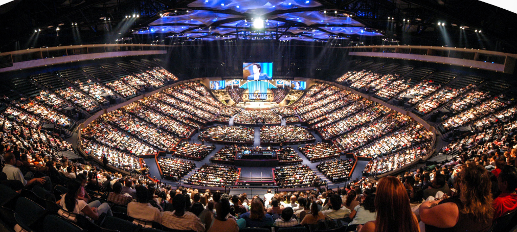 An arena-sized church building filled with people attending a worship service.
