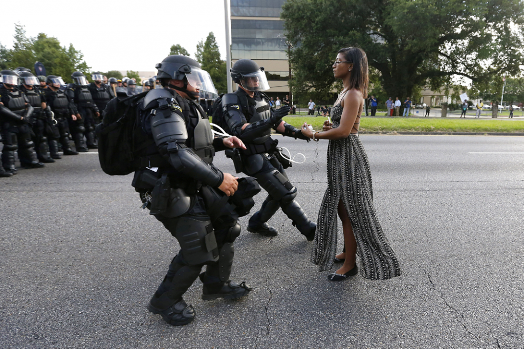 A woman stands in front of two male police officers in riot gear during a protest.